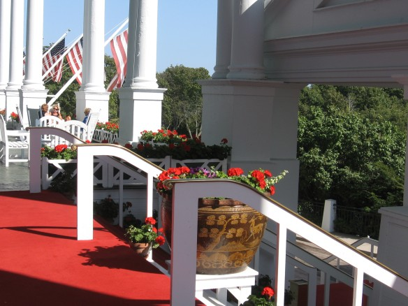 Geraniums line the steps leading from the porch to the ground level, where carriages await.