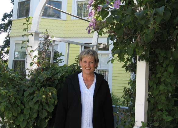Pat standing in front of a beautiful Main Street home's welcoming arbor.