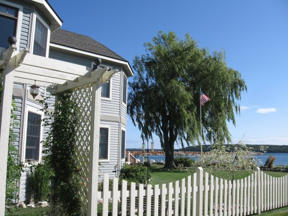 A beautiful willow tree stands in front of a home on the water close to Mission Point.