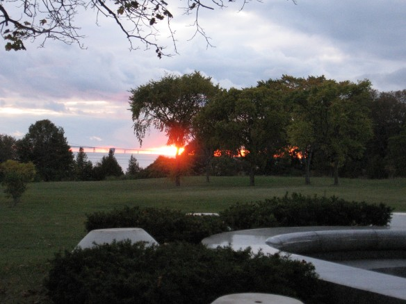 The sun going down behind the Mackinac Bridge and the trees beyond the school playground.