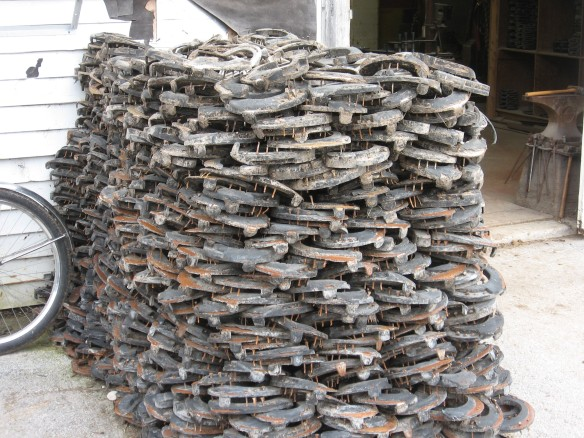 A stack of discarded horseshoes by the blacksmith's shop.  This pile has been growing all summer, and more were added when the horses' shoes were taken off when they left the island for the winter.  The rubber will be stripped off these by a special machine off the island.  Then the metal will be melted down and reused.