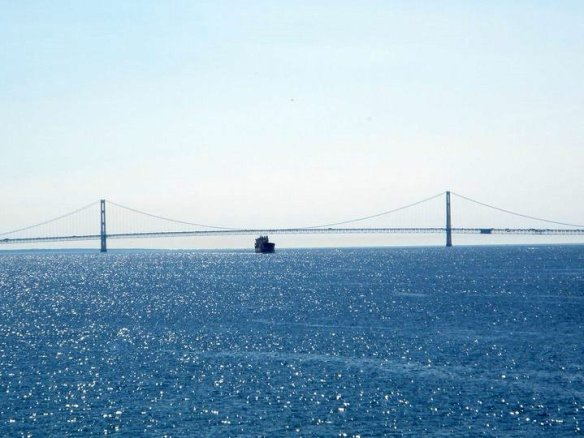 A view from Round Island of a freighter crossing under the Mackinac Bridge.
