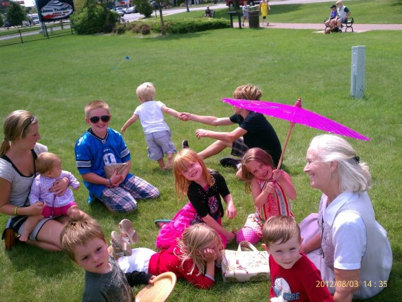 "Someone posted this pic last week on Chris Ann's Facebook page, and I just had to include it.  It shows Chris Ann and all 10 of her grandchildren last August at Conkling Heritage Park in Mackinaw City.  Chris Ann quipped: ""I was born on Queen Elizabeth's birthday, so I think I was 'holding court' with this group!"""
