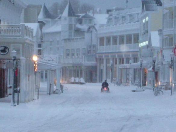 An eerie photo from downtown . . . low light, ghostly buildings, a lone snowmobiler.  (Photo: Marge Lind)