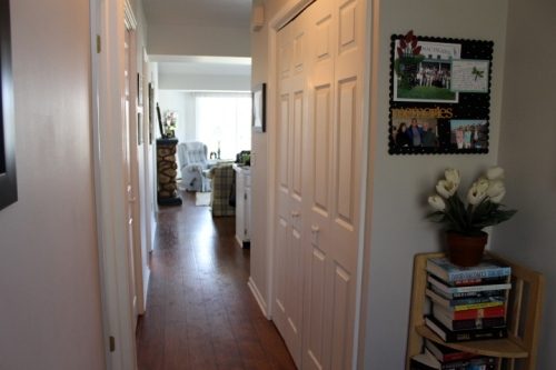 View down hall with pantry on right and laundry closet on left