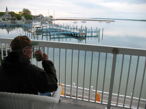 Lowell having a cup of coffee as he's sitting on the balcony overlooking the harbor.