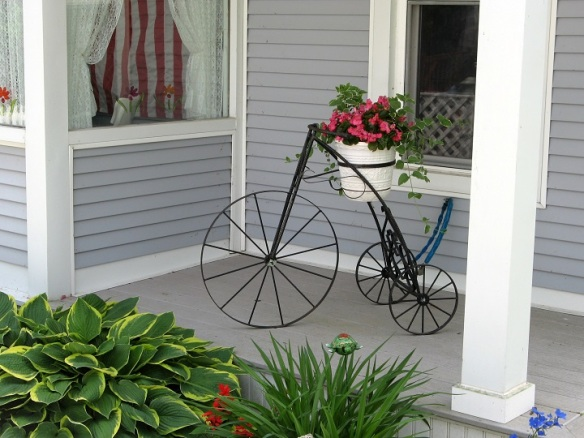 A vintage tricycle makes a great flower stand on the porch of a French Lane cottage.