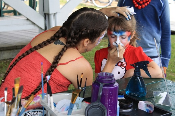 The face painting table was swamped with eager little faces waiting to be transformed into butterflies, flags