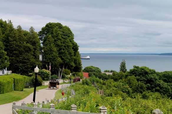 Carriages full of visitors continue their journeys down the East Bluff Road as a freighter slips out of sight around the curve of the island.