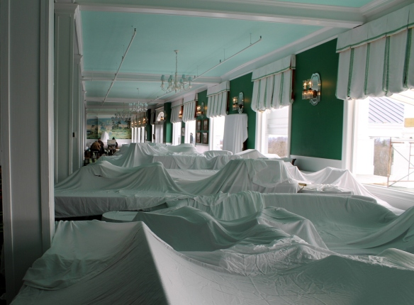 The majority of the furniture is covered in white cloths . . .