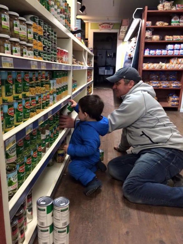 Cutest. Photo. Ever. Andrew Doud (owner of Doud's Market) patiently shows his oldest son, Louie, how to stock shelves. Generation to generation. And that's how it's done on Mackinac.