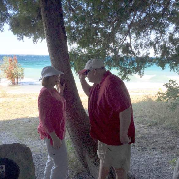 """Yesterday we visited Grand Hotel where the movie Somewhere in Time was filmed. On the bike ride today, Ted showed us the tree from the scene where Elyse first saw Richard and she said, ""Is it really you?"" Here Glen and I are standing in front of that tree."""