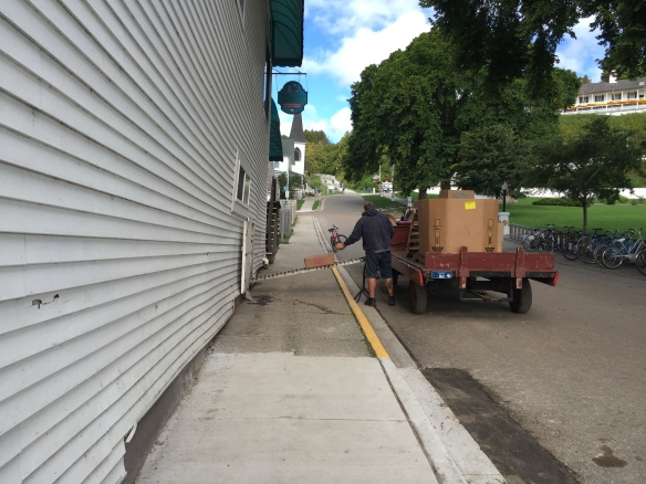 Going back home up Fort Hill, I stopped to watch groceries going by conveyer belt from a dray into the supply room of Doud's Market.
