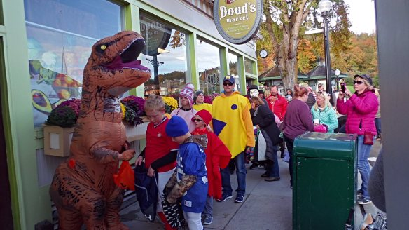 Children fill the streets for a giant parade past the downtown businesses, who pass out goodies to every trick or treater.