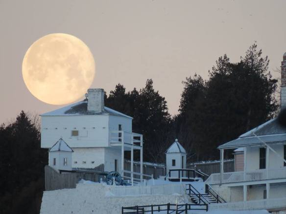 Full moon hangs over a blockhouse at Fort Mackinac.