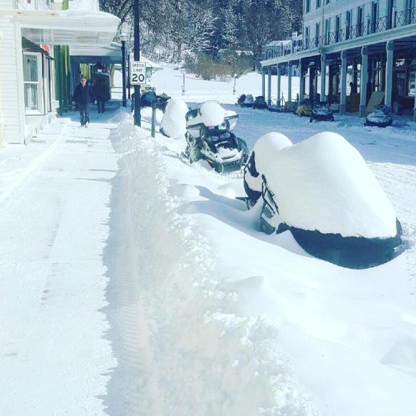 Anything sitting for any length of time was soon wearing a thick layer of snow - like these snowmobiles parked along Main Street. (Photo: Doud's Market)